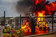 Brandskolautbildning med levande brand och brandmannen Arkivfoton