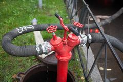 Brandslang tot een roestige rode brandkraan wordt vastgehaakt die Royalty-vrije Stock Fotografie