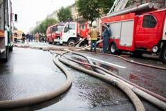 Brandslangen op de achtergrond van brandvrachtwagens en brandbestrijders op het werk Royalty-vrije Stock Foto