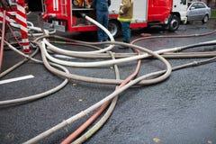 Brandslangen op de achtergrond van brandvrachtwagens en brandbestrijders op het werk Royalty-vrije Stock Afbeelding