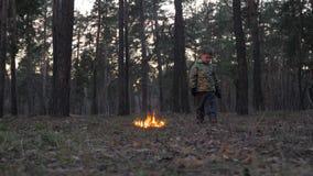 Brandstarter i skogmordbranden parkerar in Inställning av brand till naturen, flora, fauna Pojke som omkring ser, medan stå in stock video