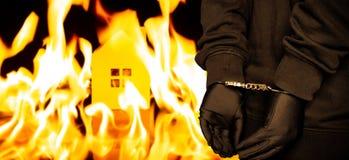 Brandstichter in handcuffs met een brandend huis op rug stock foto's