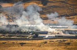 Brandstichting van industrieel pakhuis, het grote rookwolk uitspreiden met wind Massieve die schade op de bedrijfbouw of pakhuis  stock afbeelding
