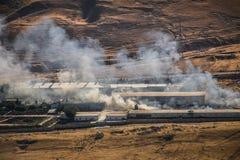 Brandstichting van industrieel pakhuis, het grote rookwolk uitspreiden met wind Massieve die schade op de bedrijfbouw of pakhuis  stock foto