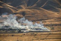 Brandstichting van industrieel pakhuis, het grote rookwolk uitspreiden met wind Massieve die schade op de bedrijfbouw of pakhuis  stock afbeeldingen