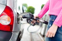 Brandstof van de dame de pompende benzine in auto bij benzinestation stock foto