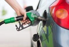 Brandstof van de mensen de pompende benzine in auto bij benzinestation