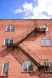 Brandtrapladder en brickwall royalty-vrije stock afbeeldingen