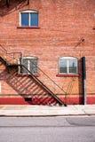 Brandtrapladder en brickwall royalty-vrije stock afbeelding