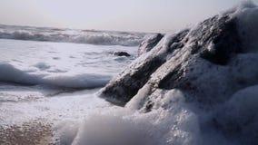Brandung, eine Welle mit Schaumfall in die Kammer nahe einem schwarzen Stein im Meer stock footage