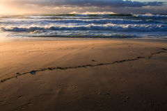 Brandung, Sand und Sonnenaufgang am Strand Lizenzfreie Stockfotos