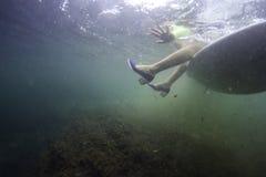 Brandungsm?dchen, das unter Wasser auf einem Surfbrett mit Schuhen sitzt stockfotografie