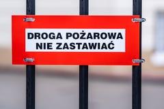 Brandvägen, håller klar text i polermedel på tecknet som monteras till vit och röd plattan för staketet, svarta bokstäver arkivfoto