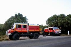 Brandvrachtwagens bij de ingang van een bosweg Stock Afbeeldingen