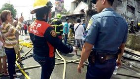 Brandvrouw het coördineren met politieman bij de plaats van de huisbrand stock video