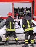 Brandweerlieden in actie na het verkeersongeval stock afbeeldingen