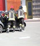 Brandweerlieden in actie tijdens het autoongeval royalty-vrije stock afbeelding