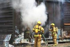 Brandweerlieden die brand werken te doven Stock Foto