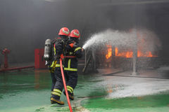 Brandweerlieden die de brand bestrijden Stock Afbeelding