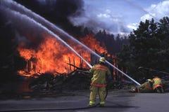 Brandweerlieden die huisbrand bestrijden Stock Afbeeldingen