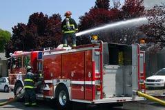 Brandweerlieden die watercanon op brandvrachtwagen gebruiken om flatbrand te doven stock foto's