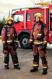 Brandweerlieden die zich naast brandvrachtwagen bevinden Stock Fotografie