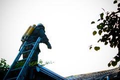 Brandweerlieden in een speciale vorm op het dak van een brandend huis Stock Foto