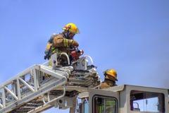 Brandweerlieden op een laddervrachtwagen Royalty-vrije Stock Foto's