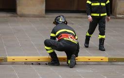 Brandweerlieden tijdens reddingsverrichtingen met een houten ladder stock foto