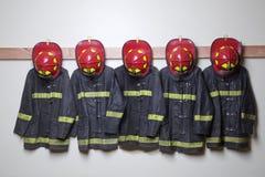 Brandweerliedenkostuums en helmen Royalty-vrije Stock Fotografie