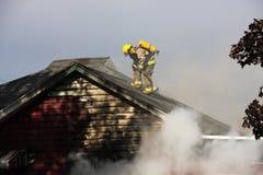 Brandweerman bovenop een brandend huis Stock Foto