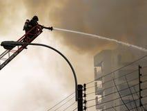 Brandweerman die een brand dooft Stock Foto