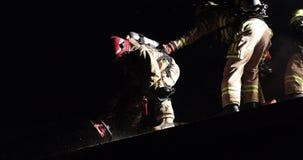 Brandweerman die zaag voor ventilatie op geïmpliceerd dak gebruiken stock video