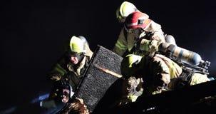 Brandweerman die zaag voor ventilatie op geïmpliceerd dak gebruiken stock videobeelden