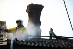 Brandweerman in een speciale vorm op het dak van een brandend huis Stock Foto