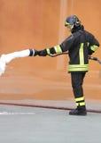 Brandweerman met een brandblusapparaat met schuim onder de Oranje rook royalty-vrije stock fotografie