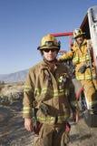 Brandweerman met Medewerker Status bij de Deur van de Brandbrigade stock foto's
