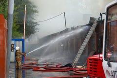Brandweerman met slang stock fotografie