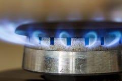 Brandwonden van aardgas omhoog sluiten de blauwe vlammen op de haardplaat van het keukenfornuis, stock foto