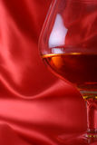 Brandy. Glass on red silk background stock photos