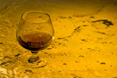 Brandy. Class of brandy on creative brown background with water Stock Photo