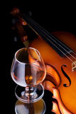 Brandy. Snifter glass of cognac and violin Stock Image