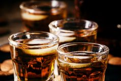 Brandy and almonds, small glasses on a dark background, selective focus royalty free stock images