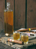 Brandy bottle, two glasses with alcohol drink and a cigar Stock Photos