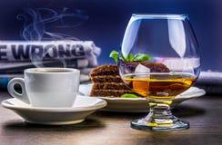 Brandy, café, torta y periódico Fotos de archivo