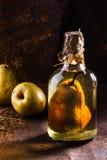 Brandy cileno con l'intera pera dentro la bottiglia Aguardiente de pera Fotografia Stock