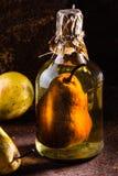 Brandy cileno con l'intera pera dentro la bottiglia Aguardiente de pera Immagini Stock