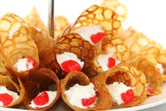 Brandy and Cream Cones. Brandy snaps wafer cones with cream and cherries Royalty Free Stock Photos