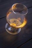 Brandy on dark wood Stock Photography