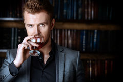 Brandy. Elegant man in a suit with glass of beverage stands in vintage room. Fashion Stock Image